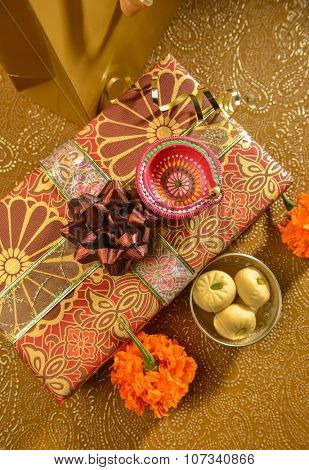 Shiny, decorative and festive gift with Indian sweet and lamp. Indian wedding or festival gifts.