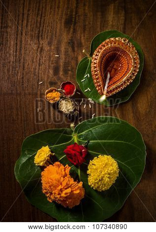 Indian devotional or puja material and objects. Ghee lamp, fresh flowers and kumkum tilak. View fro top.