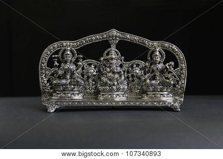 An antique statue of Lord Ganesha, Goddess Laxmi and Saraswati.