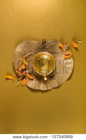 Indian earthen lamp on golden dry leaf with scattered marigold flower petals. view from above. Diwali greeting card cover.
