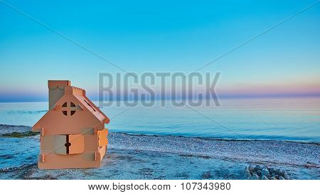 Toy house made of corrugated cardboard in the sea coast at sunset.