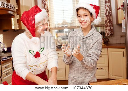 Grandmother With Grandchild In Kitchen, Christmas.