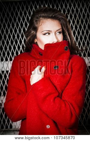 fashionable young woman portrait  wearing red coat stand in front old grid door, outdoor in the city