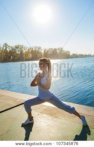 young woman in tracksuit and white undershirt   on pontoon at lake practice yoga, sunny autumn day