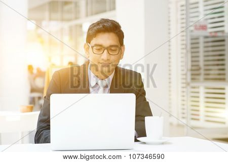 Young Asian Indian businessman using a laptop or notebook computer at cafe, with a cup of coffee. India male business man, modern building with beautiful golden sunlight as background.