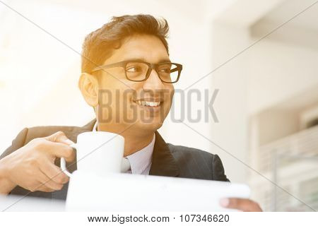 Young Asian Indian businessman using tablet pc at cafe, relaxing with a cup of coffee. India male business man, modern office building with sunlight as background.
