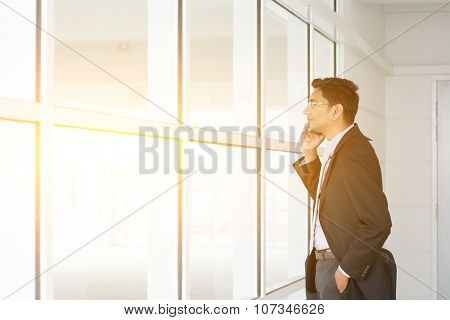 Indian man checking on new office to let and calling on phone.