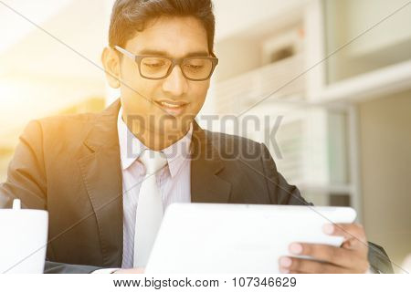 Young Asian Indian business people using tablet pc at cafe, relaxing with a cup of coffee. India male business man, modern office building with sunlight as background.