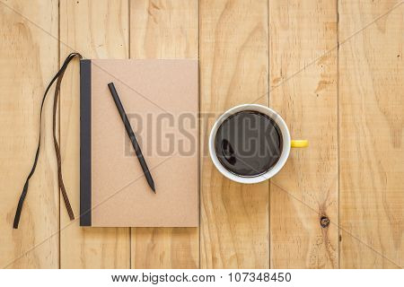 Top View Of Brown Book And Coffee Cup On Wooden Table