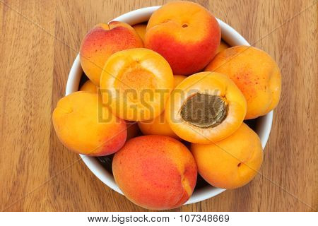 A bowl of fresh Apricots with one cut in half showing seed, on a wooden background