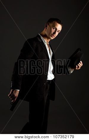 Sexy man posing as mafiosi, on gray background