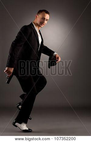 Sexy man in mafiosi costume dancing at camera