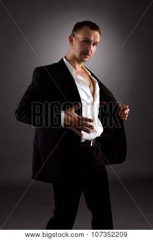 Strip dance. Attractive man in suit with stripes