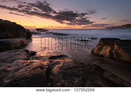 Sunrise Seascape With Rocks And Flowing Water On Long Exposure