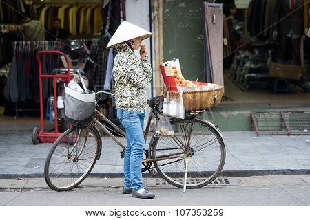 Asian vendor selling street food with traditional Vietnamese cake