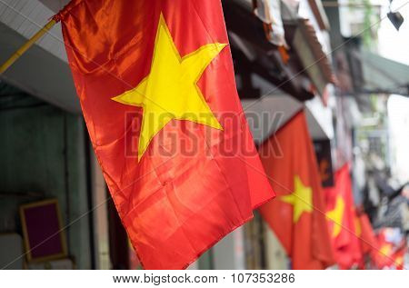 Vietnam flag on a street. Range of red flags and yellow star.