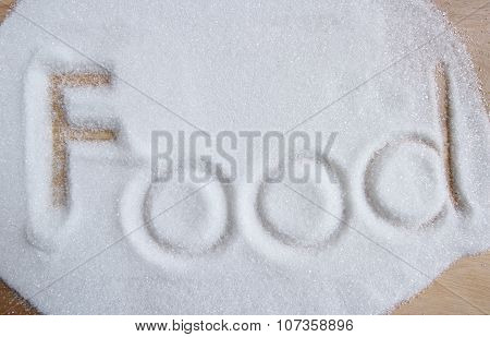 The Word Food Written Into A Pile Of White Granulated Sugar Background