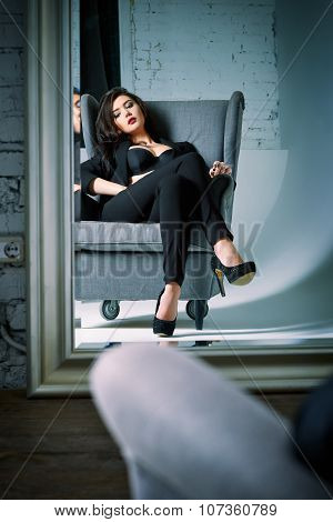 Portrait Of Beautiful Young Woman Sitting On Chair And Looking Into The Mirror