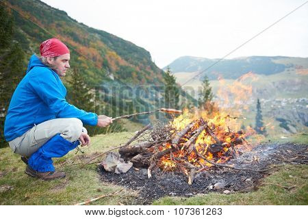 hiking man prepare tasty sausages on campfire in mountains