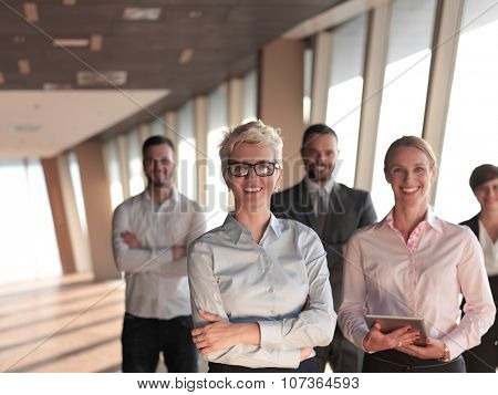 business people group standing together as team by window  in modern bright office interior