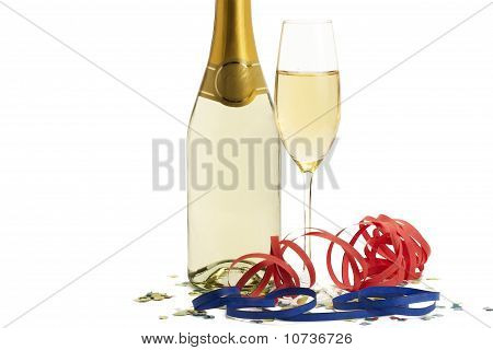 glass of champagne with blow-outs and confetti in front of a champagne bottle