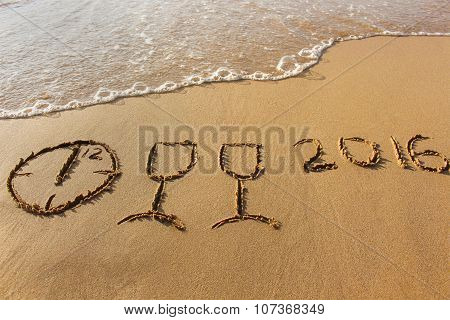 champagne glasses, clock which shows 12 hours, 2016 year written on sandy beach sea