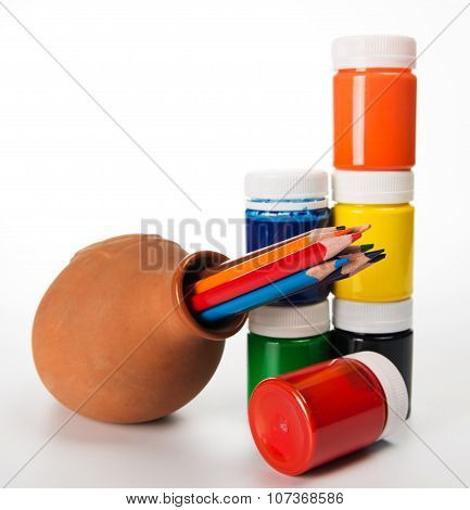 Set Of Colored Pencils And Paints For Children's Creativity In A Ceramic Jug