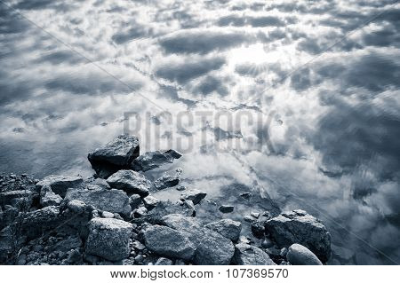 Still Lake Coast, Stones And Cloudy Sky, Monochrome