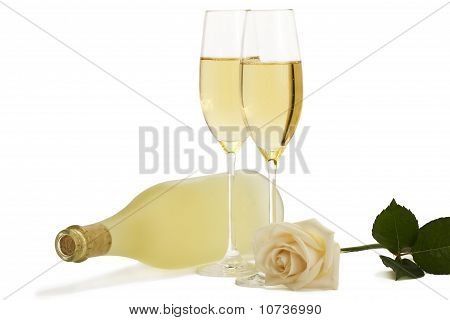 creamy rose in front of two champagne glasses and a prosecco bottle