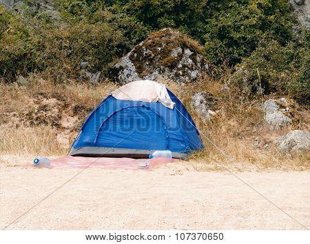 Blue tourist tent standing on the sandy beach