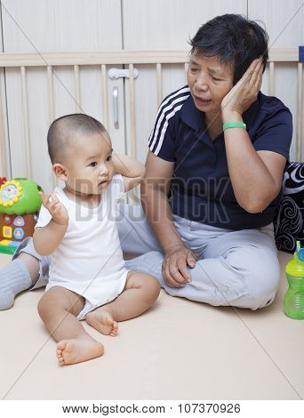 Chinese baby boy playing with grandma