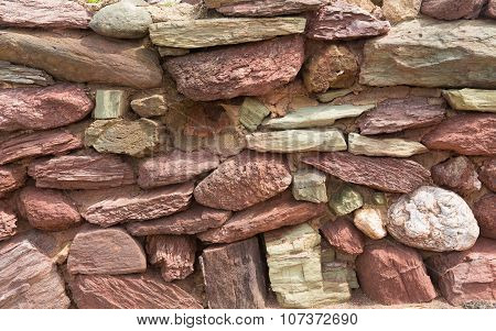 Dry stone wall with red and pink stones traditional structure with no mortar Devon England UK