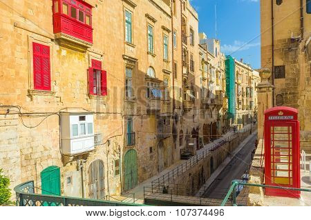 Streetview of Valletta with traditional red balconies, old red phone booth and blue sky - Malta