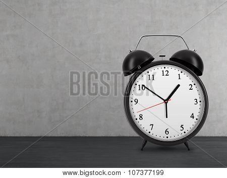 A Black Alarm Clock Is On The Black Floor. Concrete Wall.