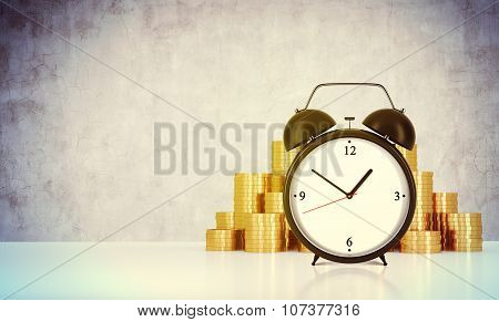 An Alarm Clock And Golden Coins Are On The Table In A Room With Concrete Wall. A Concept Of Time Man
