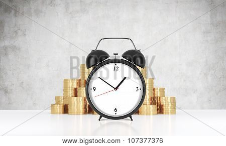 An Alarm Clock Is On The Foreground And Golden Coins Which Are On The Background.a Concrete Wall. A