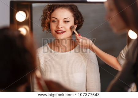 Attractive girl sitting in front of the mirror