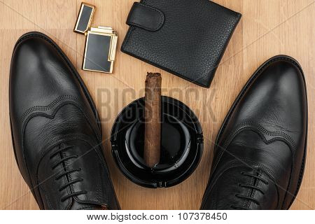 Male still life, classic men's shoes and a cigar in an ashtray