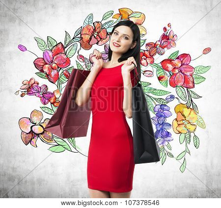 A Happy Brunette Woman Holds Colourful Bags From Fancy Shops. The Concept Of Shopping. A Sketch Of D
