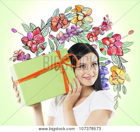 A Curious Brunette Woman Tries To Guess What Is Inside The Green Gift Box. The Sketch Of Colourful F