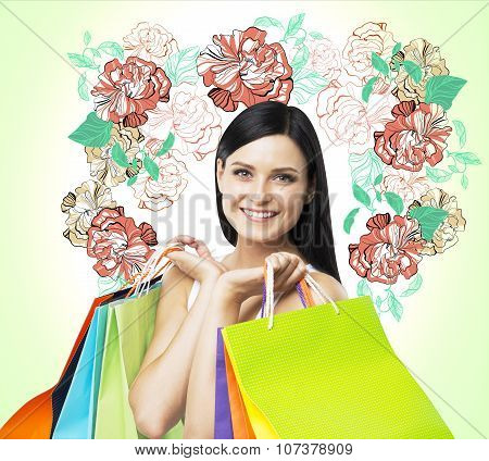 A Smiling Brunette Woman Holds Colourful Bags From Fancy Shops. The Concept Of Shopping. A Sketch Of