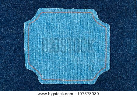 Figured frame of denim fabric with yellow stitching lies on dark jeans