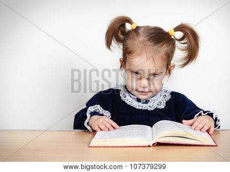 Funny Little Girl Reading Book With Glasses