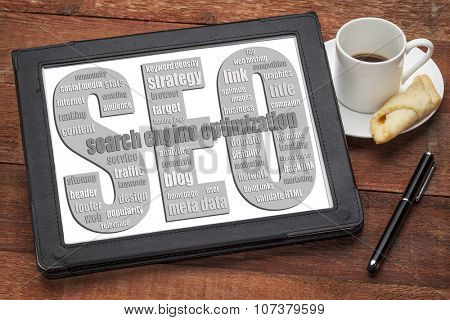 SEO - search engine optimization word cloud  on a digital tablet with a cup of coffee