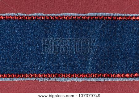 Fashionable  texture,  jeans and red  rhinestones on a red silk