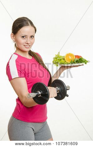 Sportswoman Holding A Dumbbell And A Bowl Of Fruit