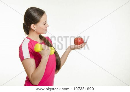 Athlete Shakes Muscles Of The Right Hand Dumbbell And Looking At An Apple In Her Left Hand