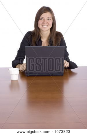 Smilling Woman At The Table With Notebook