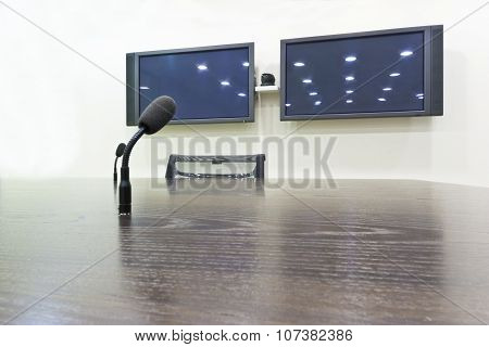 Black microphone on a wooden brown table in a city conference room with two TV screens with light re