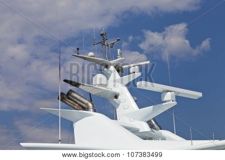 Modern super yacht radar and antennas against clouds background